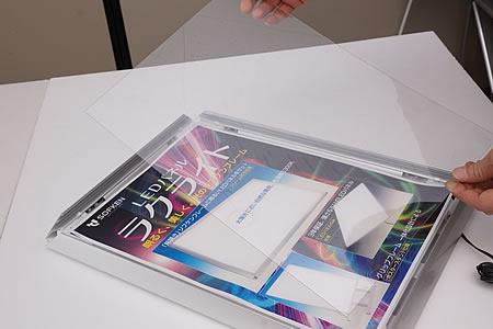 作品の上に透明板をセットしてください。  背面の各コーナーに2個ずつ計8個のスライドロックを取り付けます。