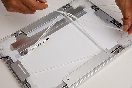 作品の下辺のフラップの穴2カ所を使って、フラップ3つの穴、計4カ所にヒモを通します。