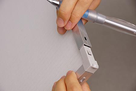 留め具を押し込んだら、フレームの一辺をゆっくりと外側にずらしていきます。