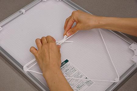 作品に対して吊り下げヒモで逆三角形を描くようにして、ヒモを結んでください。