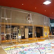 展示会場にて組み立て ── 主役はアートですが、脇役の巨大スタンドが私たちソフケンの作品です。