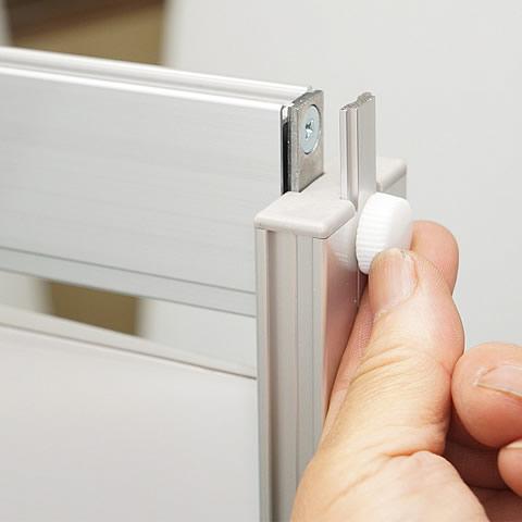 左右の支柱の上部にある白いネジを回して緩め、上辺を上方向にゆっくりとスライドさせます。(2)