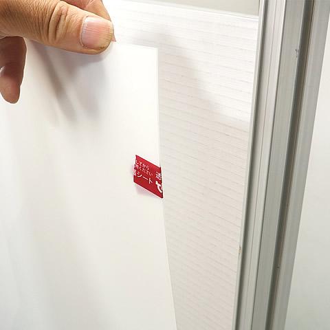 透明板の上部を少し手前に引き出してすき間を作り、ポスターを出し入れすることができます。(1)